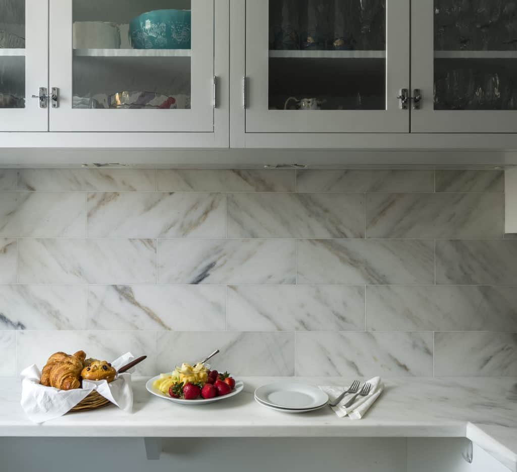 Kitchen backsplash crafted of Danby Imperial marble with matching counters cues a crisp, clean, elegant look. Photo credit: Artistic Tile.