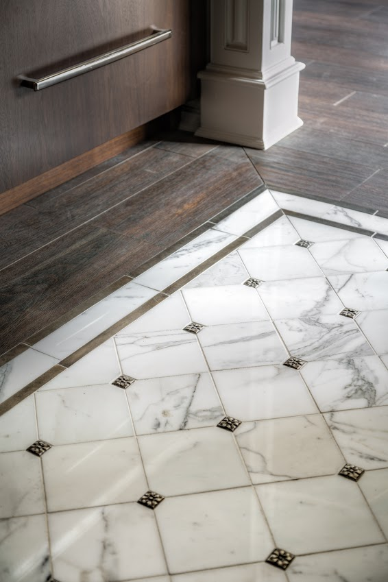 Calacatta Gold marble floor tile with decorative inserts create an elegant floor medallion in this kitchen. Photo Credit: Artistic Tile