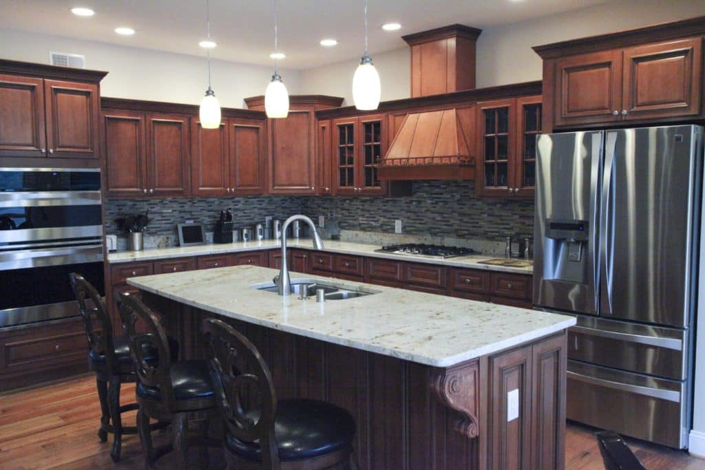 Matching granite perimeter counters and island top in this kitchen plays well with its traditional style. Photo credit: Granite America