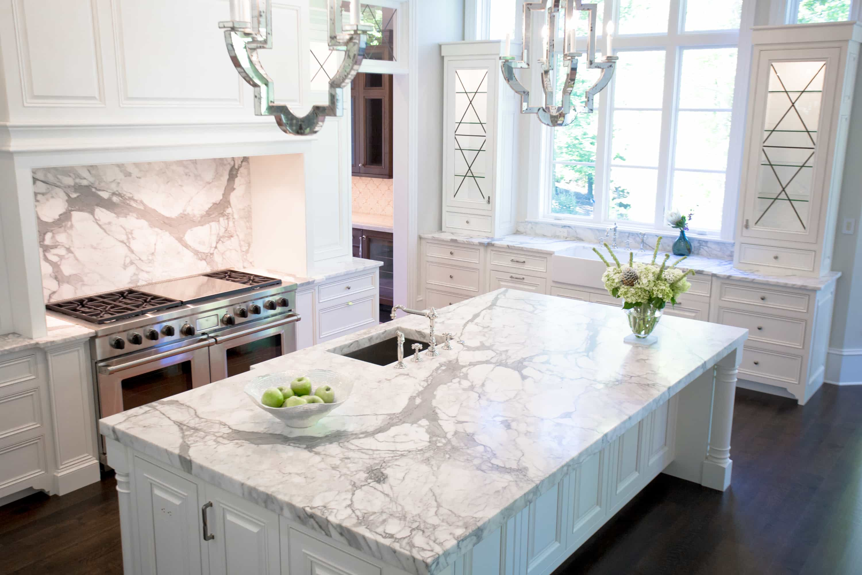 Calacatta marble from ROCKin'teriors defines the transitional look of this luxury kitchen with its rich gray veining that plays off the white cabinets. Photo credit: ROCKin'teriors