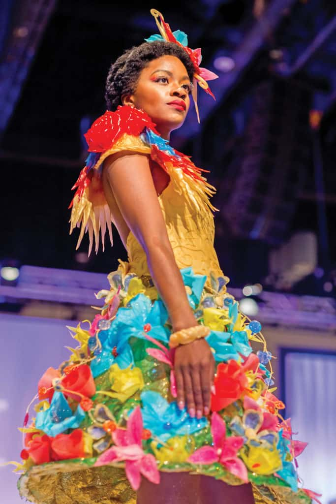 Models struts the catwalk wearing an outfit crafted of candied flowers for the Sugar Art Fashion Show. photo credit: The Americas Cake Fair