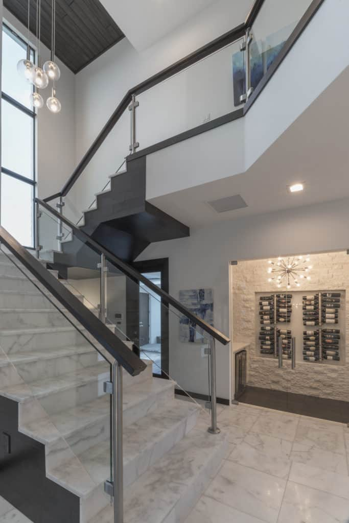 The glass and wood staircase in The Design Tourist's personal home features espresso wood handrails with chrome supports and marble stairs with mitered wood cladding on the sides.