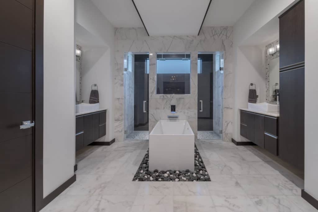The master bathroom in The Design Tourist's personal residence draws inspiration from boutique hotels with a zen/spa-like ambiance created with natural elements including a bed of river rocks below the freestanding tub and porcelain shower tile that mimics the look of espresso wood used throughout the home.