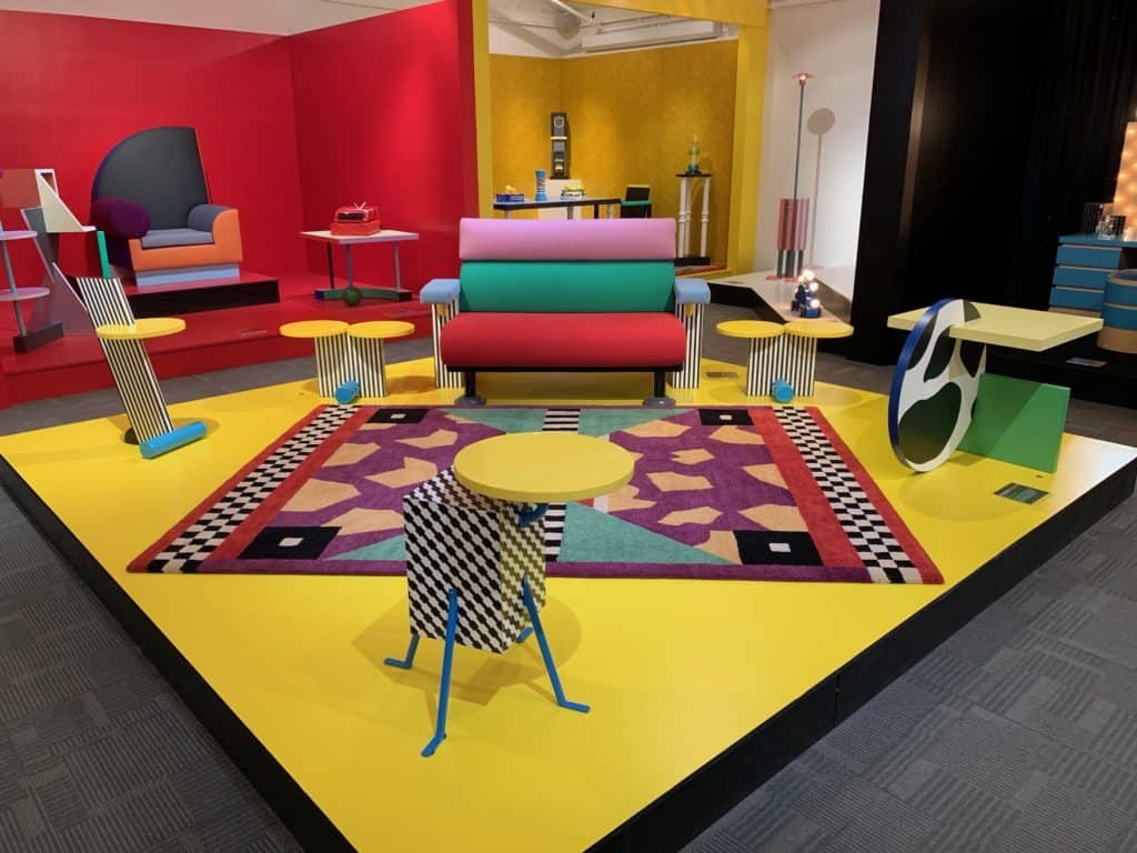 Pictured in this vignette is the Lido Sofa designed in 1982 by Michele De Lucchi for Memphis and the Continental side table designed in 1984 by Michele De Lucchi for Memphis, crafted of laminated wood and plastic. Rug by Nathalie du Pasquier Photo Credit: The Design Tourist. Both pieces were originally owned by David Bowie.