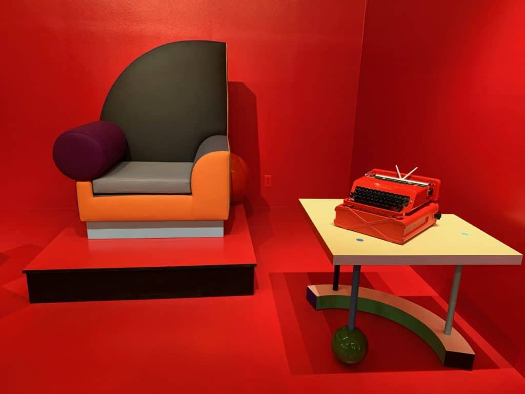The Bel Air Chair designed in 1982 by Peter Shire and the Valentine typewriter designed in 1968 by Ettore Sottsass. This red typewriter is made of ABS plastic. Sottsass created the typewriter before his involvement in the Memphis Group. He designed it in collaboration with British designer Perry King for Olivetti it was groundbreaking for its pop sensibility and bright color. Photo credit: The Design Tourist