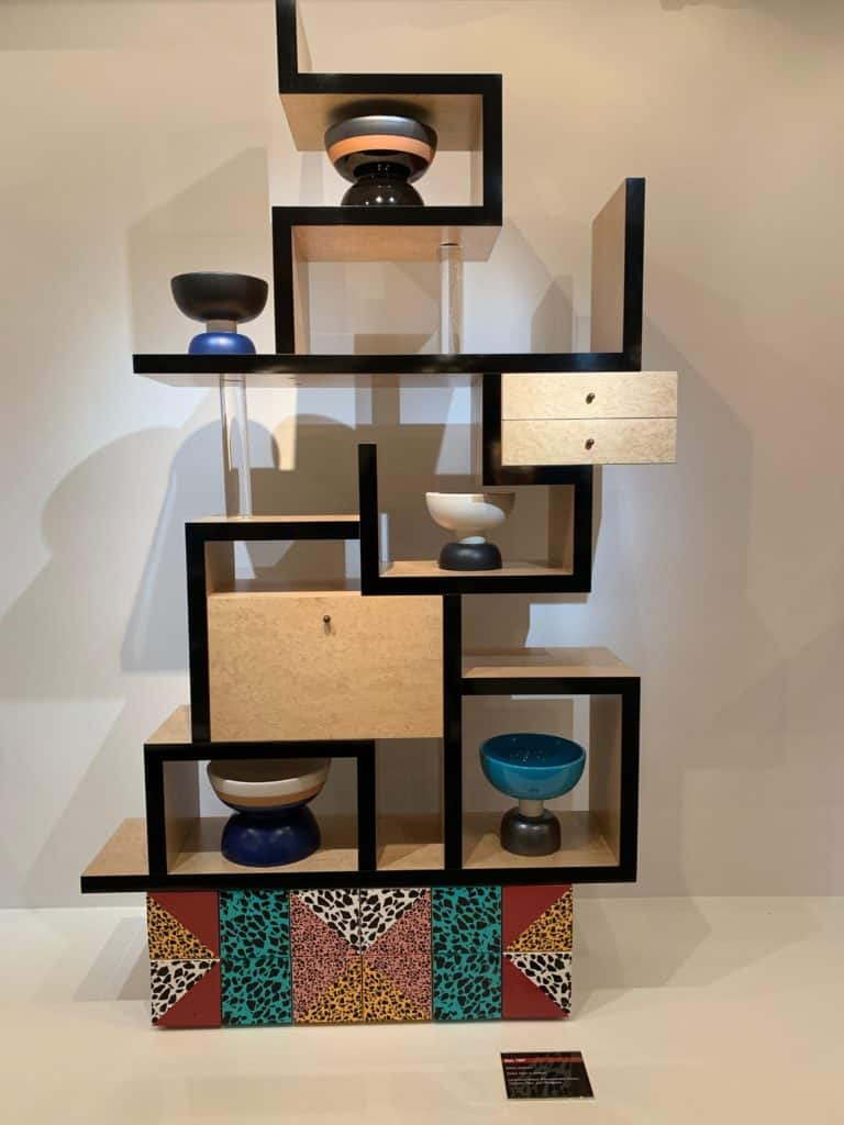 Max, 1987 by Ettore Sottsass. This shelf from the Memphis Group is made of lacquered wood and reconstituted veneer terrazzo tiles and plexiglass. Photo credit: The Design Tourist