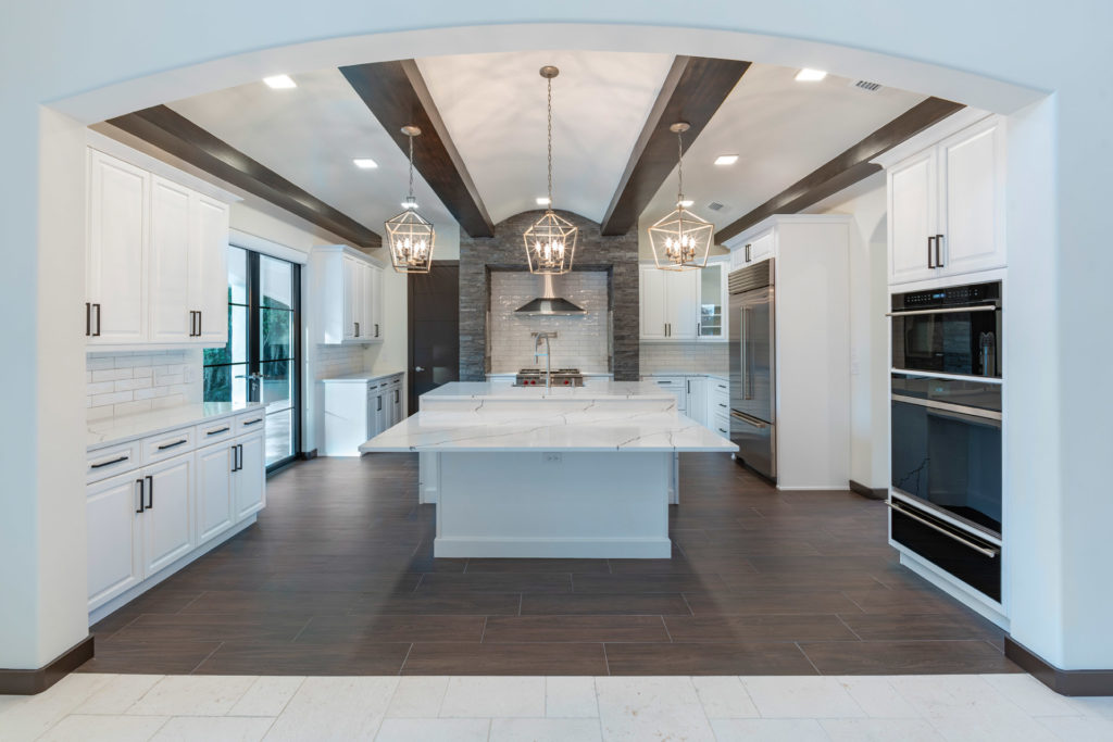 This kitchen backsplash features rough-hewn subway tile to add dimension and visual contrast to the white painted cabinets with matte black hardware. Photo credit: Orlando Custom Home Builder Jorge Ulibarri.