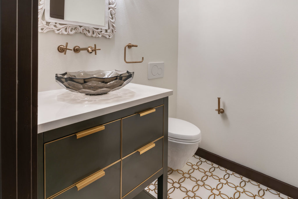 Brushed brass cabinet hardware and faucets complement brass inlays in the tile flooring in this powder bath. The home is designed and built by Orlando Custom Homebuilder Jorge Ulibarri. www.cornerstonecustomconstruction.com
