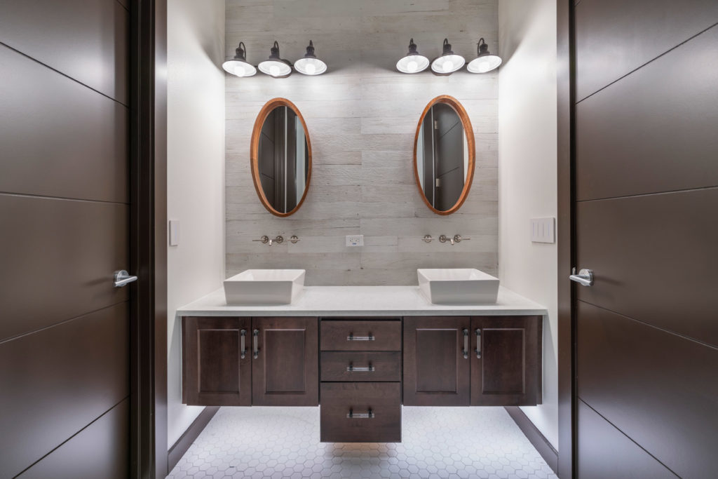 Another transitional style mashup is in this bathroom by Orlando Custom Home Builder Jorge Ulibarri. Notice the industrial-styled vanity lights paired with geometric sleek vessel sinks and modern octagon mosaic floor tile with rustic textured porcelain wood look tile on the backsplash.
