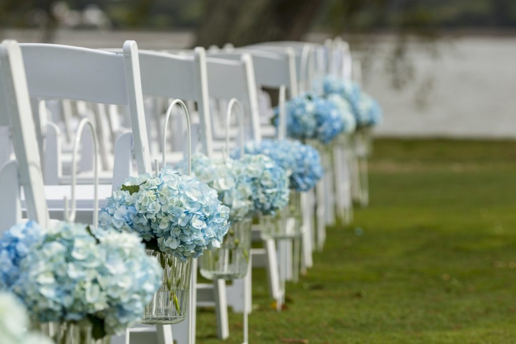 Bouquets of hydrangeas hanging from chairs for outdoor wedding.
