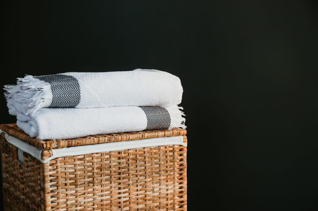 White cotton towels on a rattan box against black wall in a laundry.
