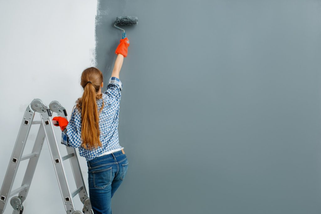 Female house painter paints walls indoor