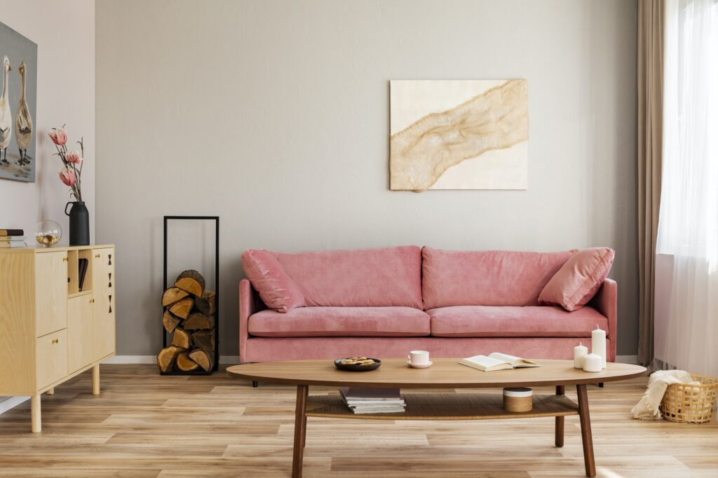 Pastel abstract painting on beige wall behind velvet pink settee in simple living room