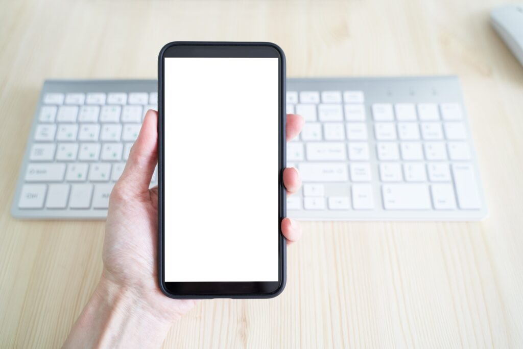 Unrecognizable person hold cell phone. View from behind, mockup with white phone display