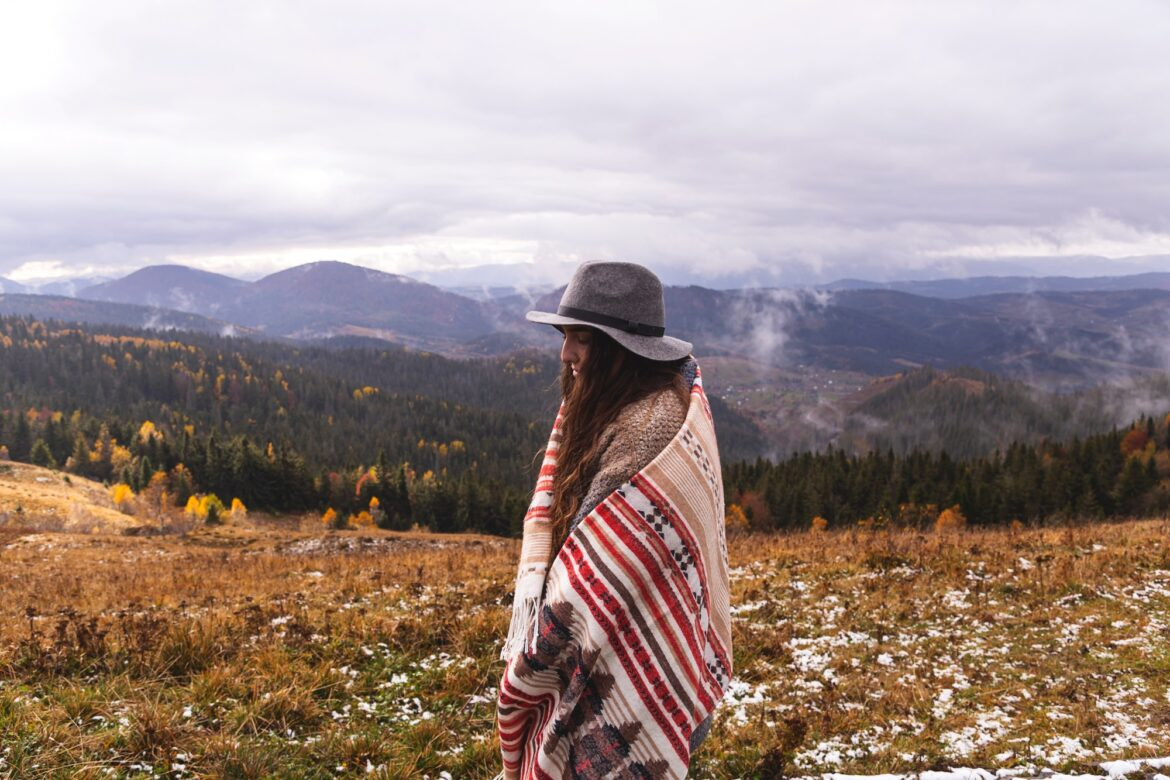 Girl traveler in the mountains in boho clothes with a hat. Enjoys nature and travel. Local camping