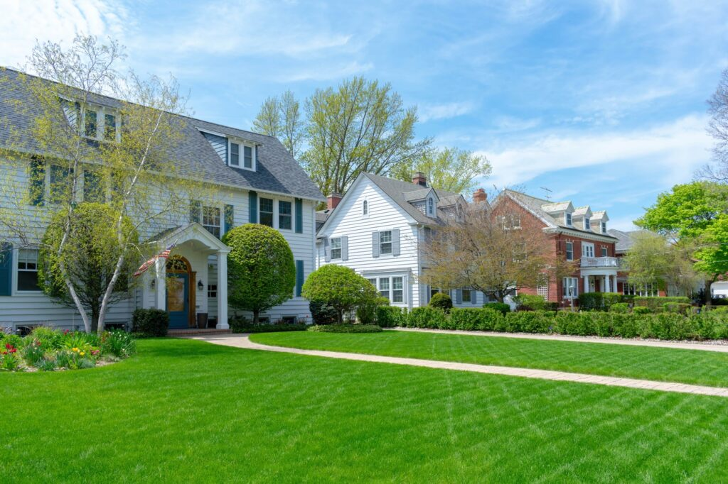 Row of traditional suburban homes with lush green front lawns in nice residential neighborhood -