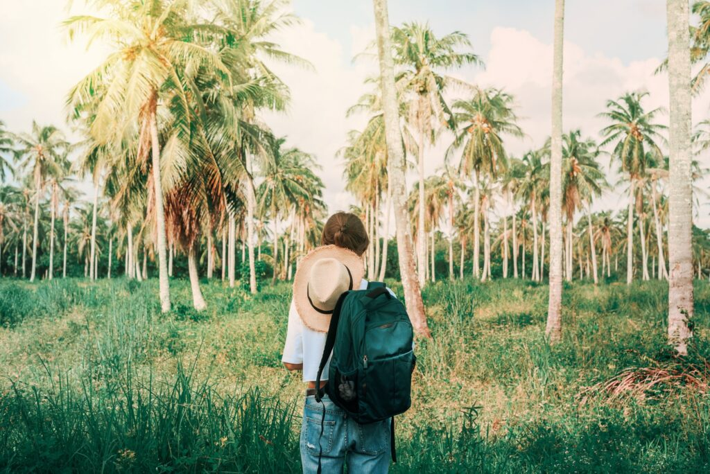 Young woman with backpack from behind in the tropics