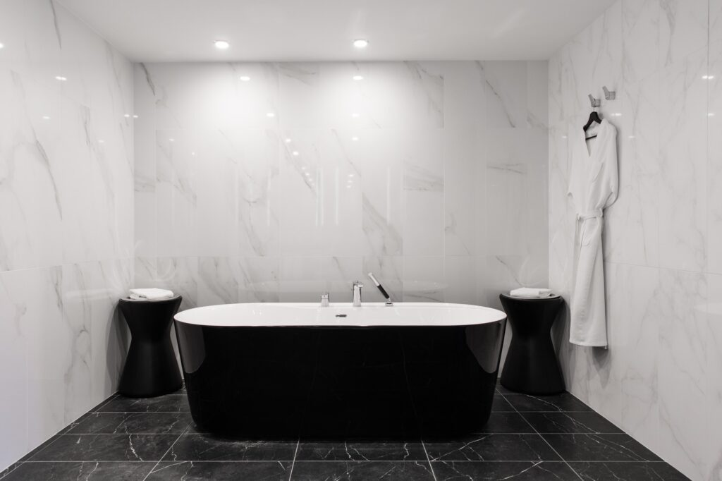 Freestanding black bathtub, stylish minimalist black and white loft style bathroom. Bath, washstand