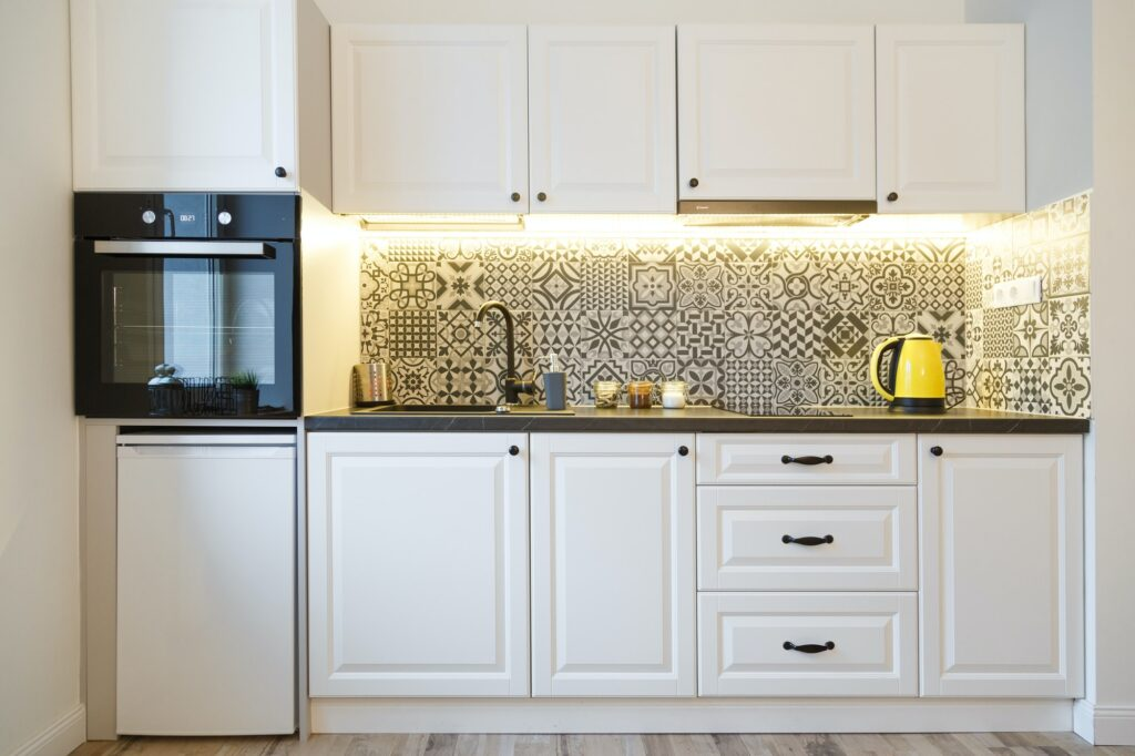 Beautiful home kitchen with white cabinets and backlight