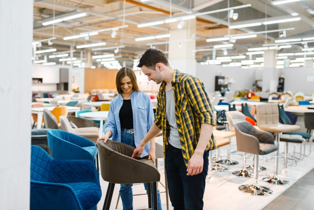 Couple choosing bar chair in furniture store