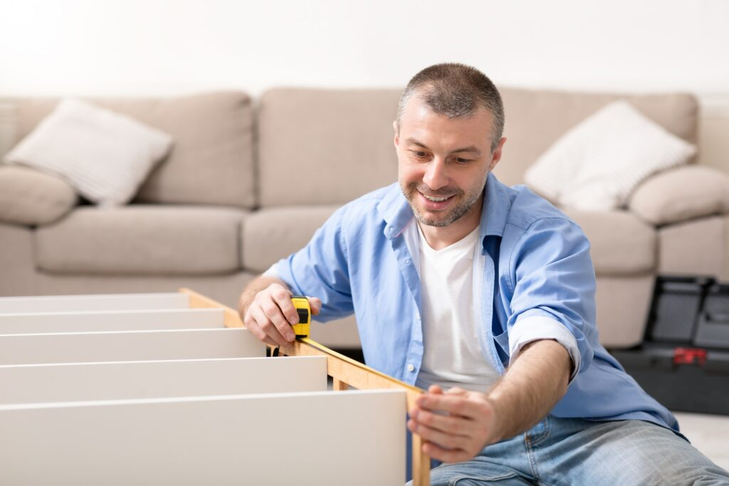 Handyman With Measuring Tape Assembling Shelf At Home