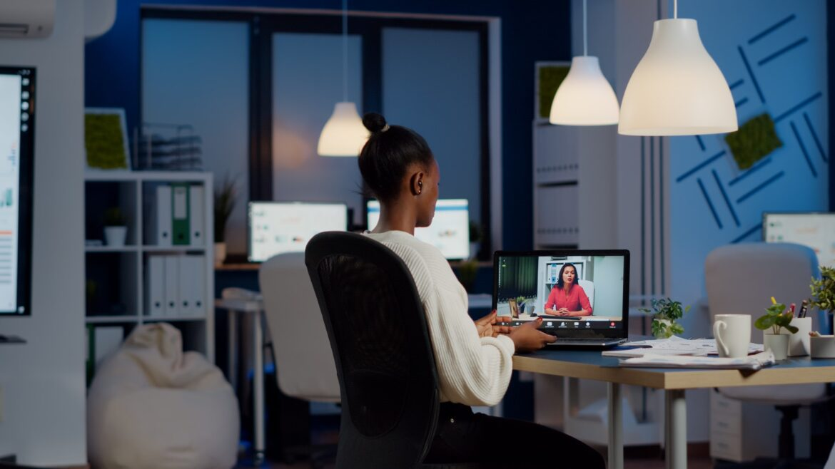African freelancer working remotely discussing with woman partner online