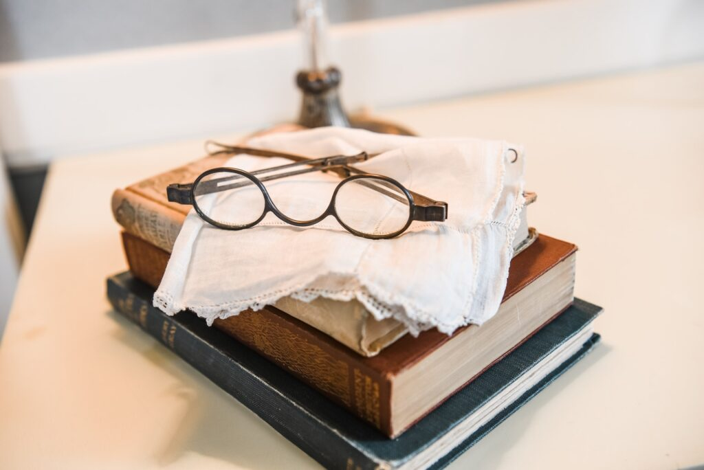 Antique glasses, a handkerchief, and books on a nightstand.