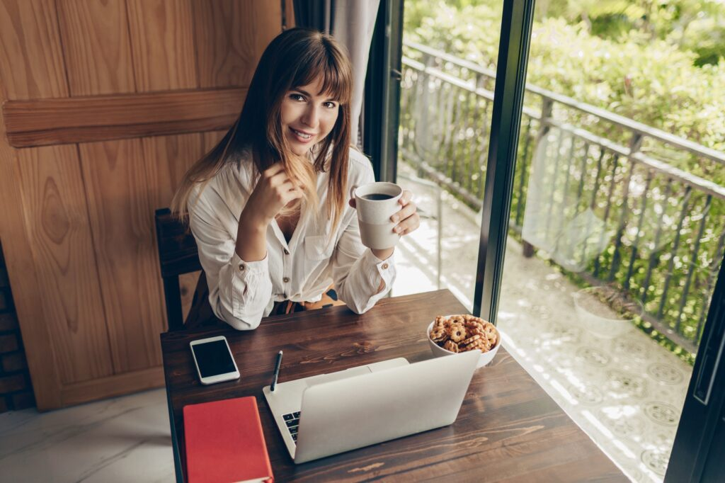 Happy freelance female worker sitting at home with cup of coffee