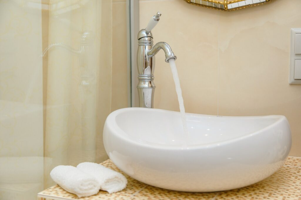 Water pours out of the tap. Modern bathroom interior.