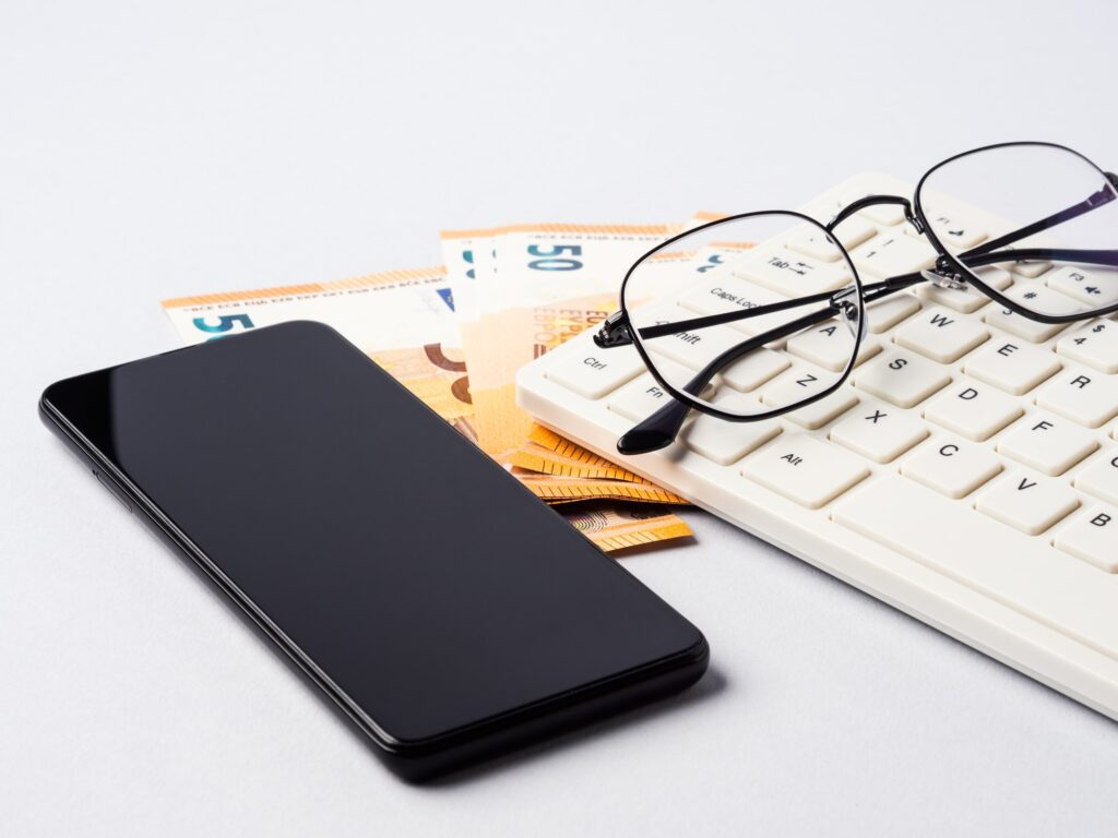 Euro money banknotes, keyboard, smartphone and glasses, online banking, business, student loan