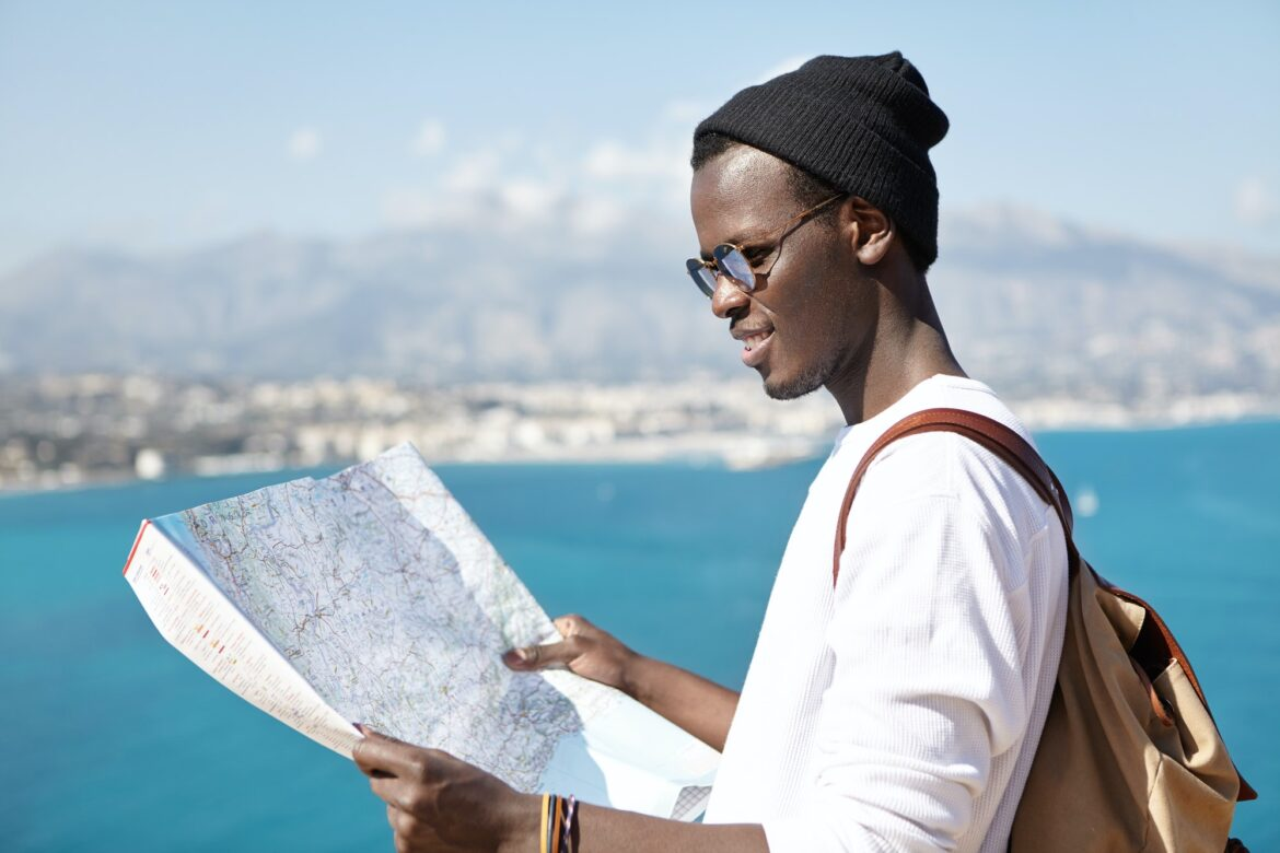 Side view of smiling trendy looking young dark-skinned hitchhiker studying paper map in his hands, p